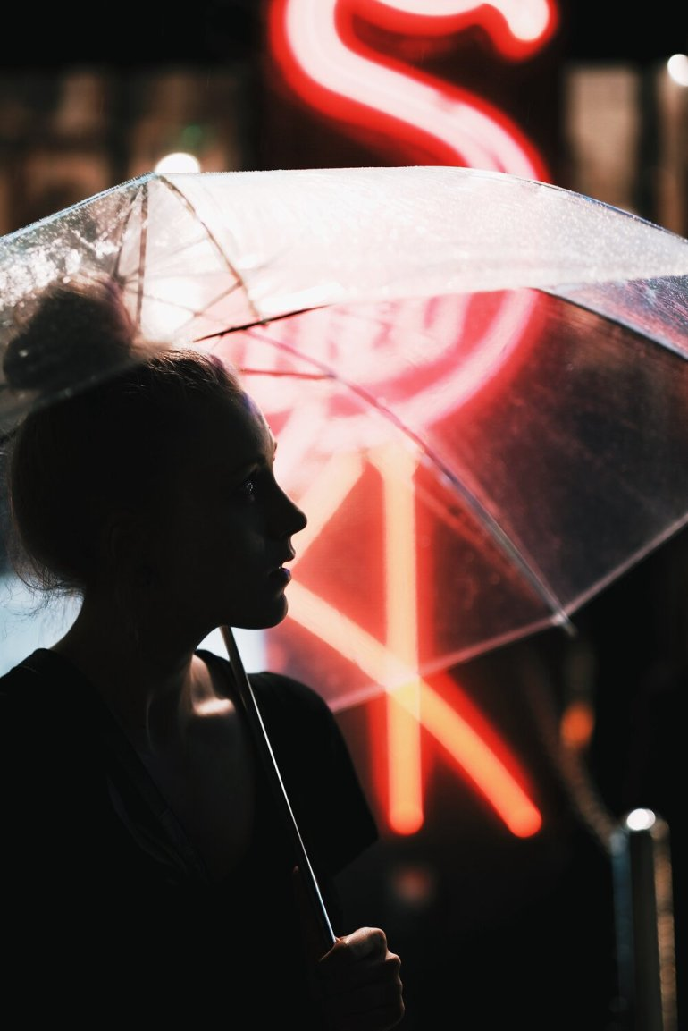 """A woman with a transparent umbrella in front of a red neon sign."" by  Oskar Krawczyk  on  Unsplash"